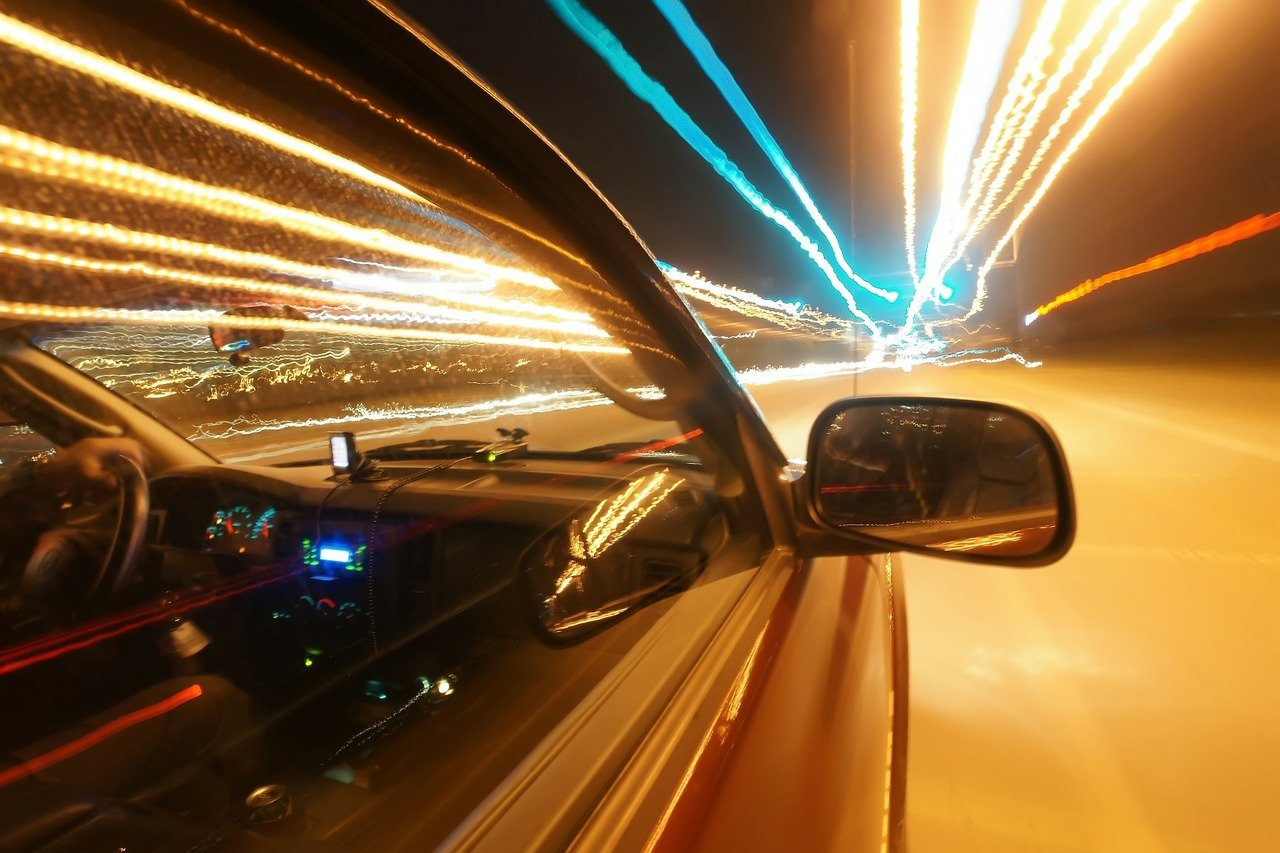 Car driving on brightly lit road